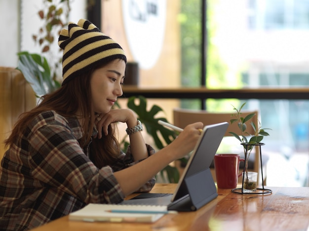 Side view of female teenager working with tablet and stationery in cafe