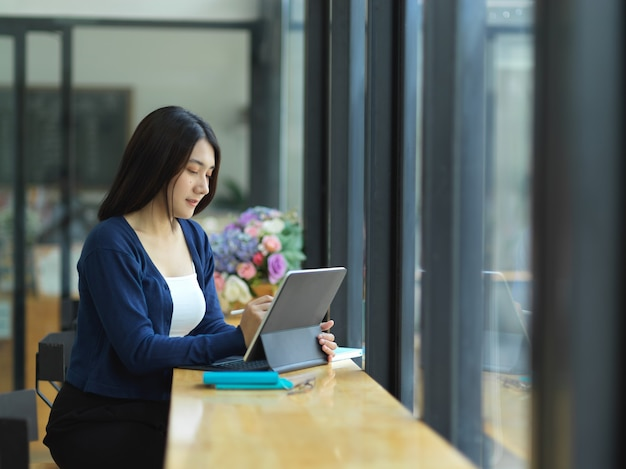 Side view of female university student doing homework with digital tablet in cafe