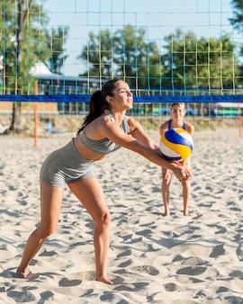 Vista laterale dei giocatori di pallavolo femminile che giocano sulla spiaggia