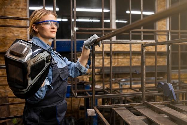 Vista laterale del saldatore femminile al lavoro