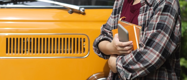 Side view of female worker holding notebooks and smartphone while standing in front of her car