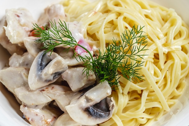 Fettuccini alfredo di vista laterale con la salsa e l'aneto di funghi arrostiti su un piatto
