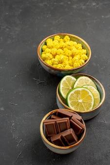 Vista laterale di dolci da lontano in ciotole di cioccolato lime e caramelle gialle sulla superficie scura