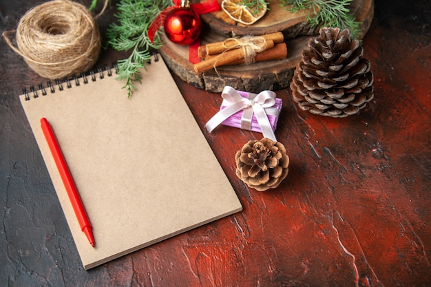 Vista laterale di rami di abete e quaderno a spirale chiuso con penna cannella lime cono di conifere e palla di corda su sfondo scuro