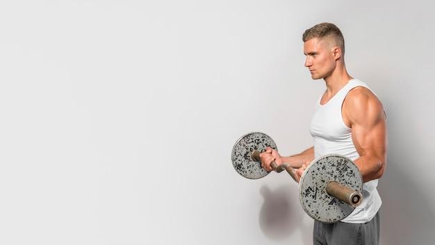 Vista laterale dell'uomo in forma in posa tenendo i pesi