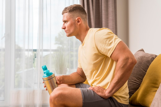 Side view of fit man relaxing on couch after working out