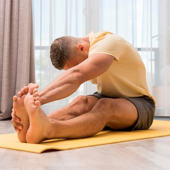 Side view of fit man stretching before working out at home