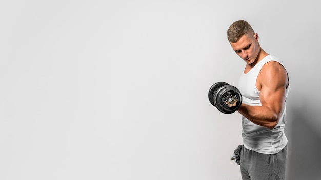 Side view of fit man with tank top using weights