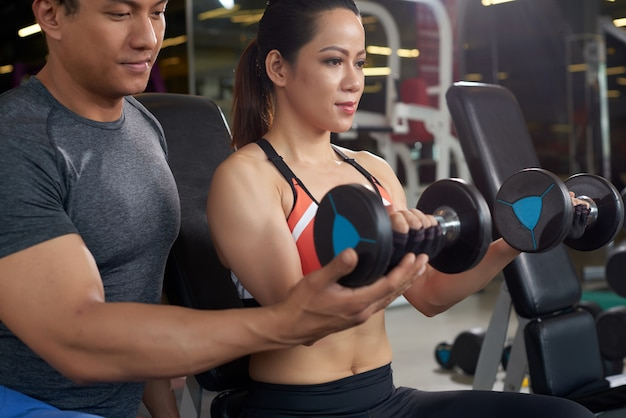 Side view of fit woman working out with personal trainer weightlifting
