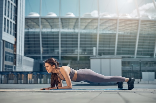 Side view of a fit young female athlete doing a plank exercise on the ground
