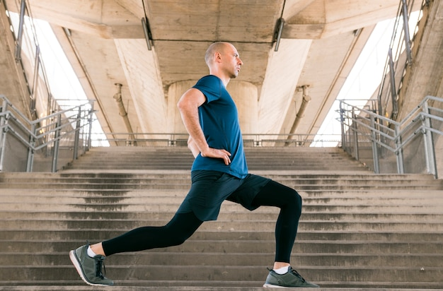 Side view of a fitness man doing stretching exercises standing on staircase