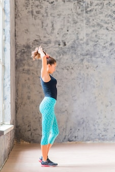 Side view of a fitness young woman standing against concrete wall tying her hair