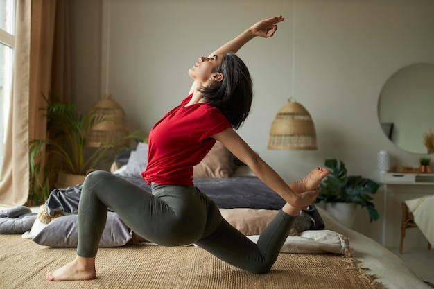 Side view of flexible young female advanced yogi exercising indoors doing eka pada rajakapotasana pose or one-legged king pigeon posture ii, stretching front of torso, ankles, thighs and groins