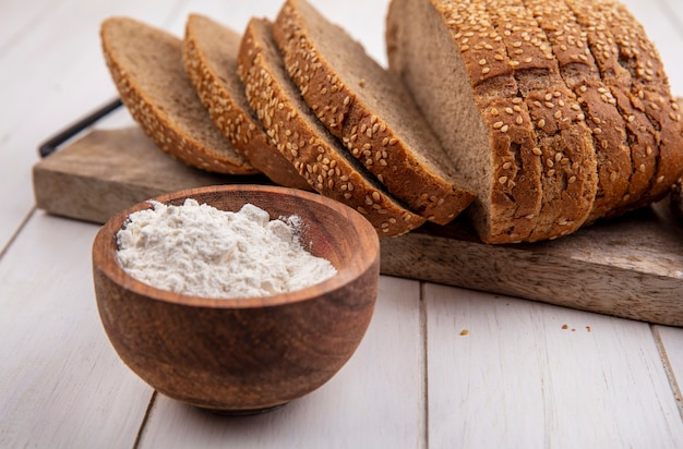 Side view of flour in bowl with seeded brown cob on cutting board on wooden background