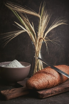 Side view flour in bowl with wheat, knife and bread on dark brown. vertical