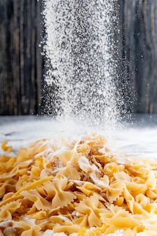 Side view of flour falling on bow tie or farfalle pasta on black background