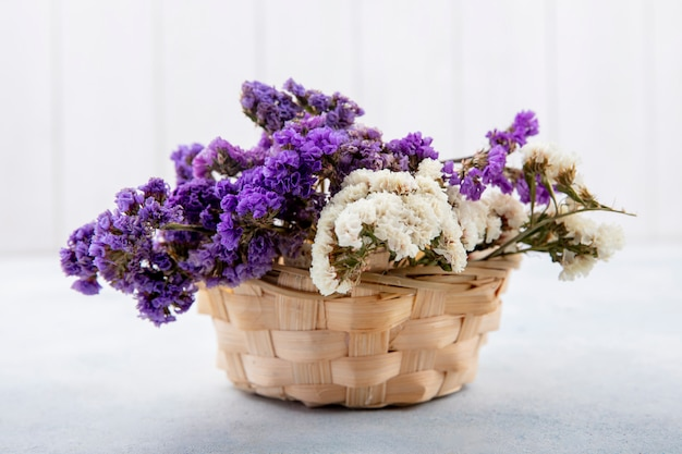 Side view of flowers in basket on white surface