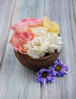 Vista laterale di fiori in una ciotola su sfondo di legno