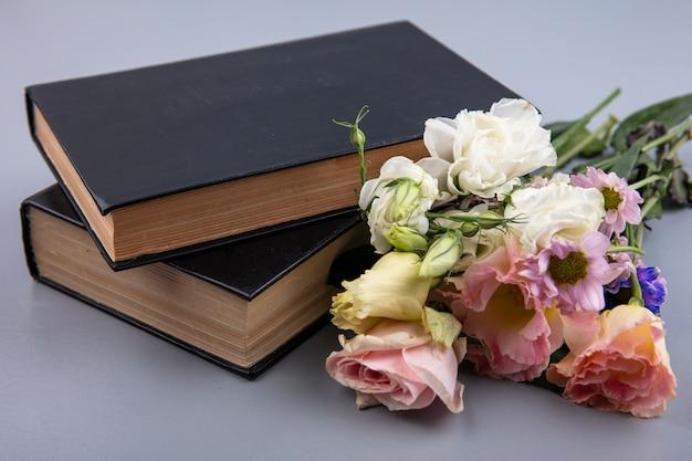 Vista laterale di fiori e libri chiusi su sfondo grigio