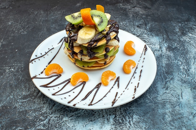 Side view of fluffy american-style pancakes made with natural yogurt and stacked with layers of fruit decorated with chocolate on white plate on ice background