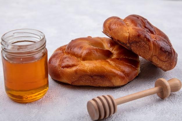 Vista laterale di soffici e morbidi panini con miele su un barattolo di vetro e un cucchiaio di miele in legno su uno sfondo bianco
