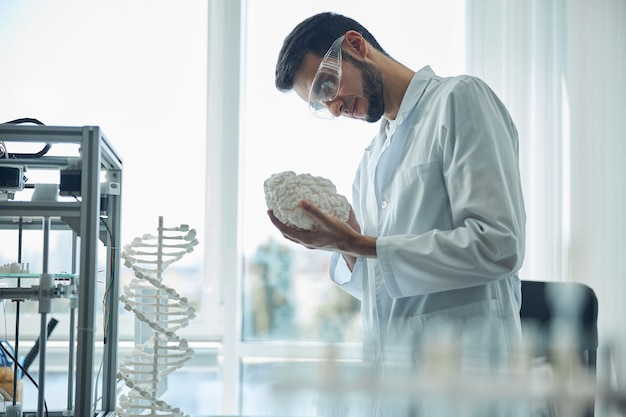 Side view of a focused dark-haired bearded medical student holding the 3d printed brain model
