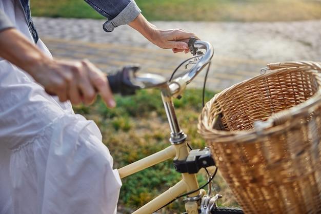 야외에서 자전거 핸들을 잡고 있는 여성 손의 측면 보기 초점 이미지