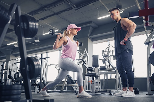 Side view of focused and motivated sporty young blonde girl in sportswear doing legs exercises while handsome muscular personal trainer monitoring her in the gym