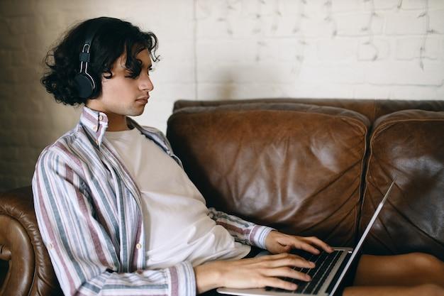 Vista laterale del giovane maschio concentrato sul divano in pelle con il computer portatile in grembo utilizzando cuffie wireless ascoltando musica o giocando online, comunicando con altri giocatori tramite chat vocale