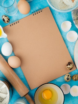 Side view of foods as egg egg yolk with water and rolling pin on blue background with copy space