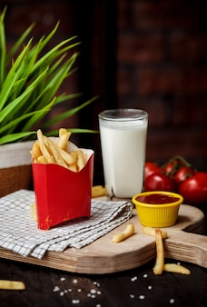 Vista laterale delle patate fritte in borsa del cartone con ketchup sul tagliere di legno