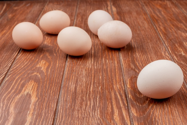 Side view of fresh chicken eggs isolated on a wooden background