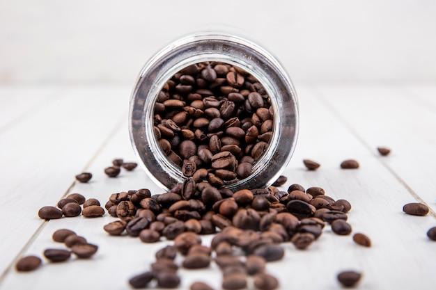 Side view of fresh coffee beans falling out of a glass jar on a white wooden background