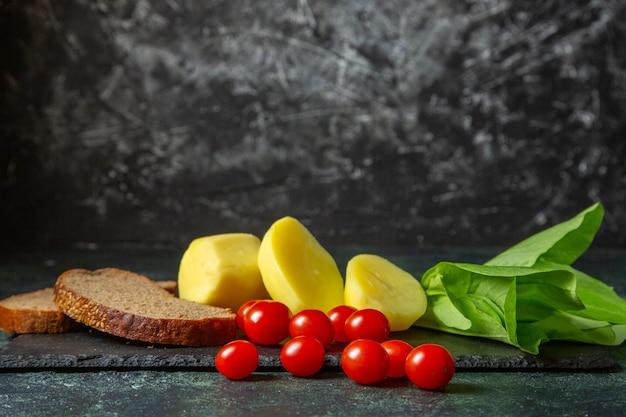 Vista laterale di patate fresche tagliate e fette di pane dietetico pomodori fascio verde sul tagliere di legno su sfondo di colori mescolare nero verde con spazio libero