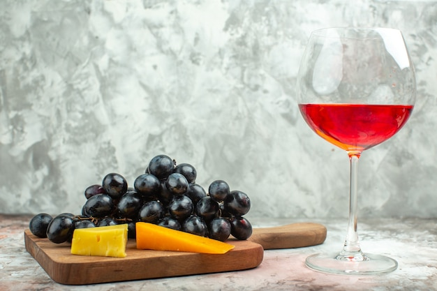 Side view of fresh delicious black grape bunch and cheese on wooden cutting board and a glass of wine on mixed color background