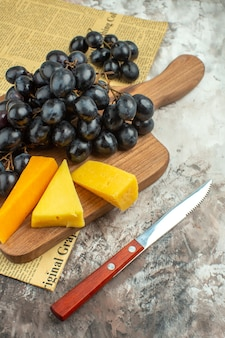 Side view of fresh delicious black grape bunch and various kinds of cheese on wooden cutting board