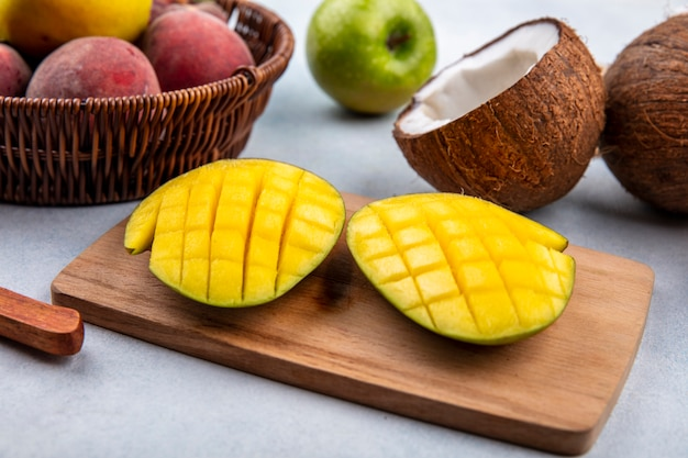 Side view of fresh and delicious fruits like sliced mango on a wooden kitchen board with peaches on a bucket green apple and half coconut on white surface