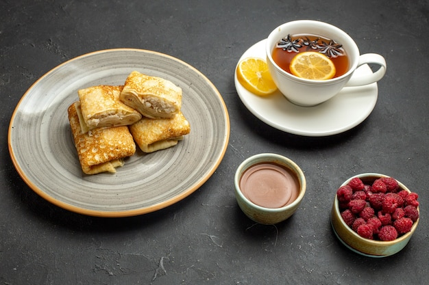 Vista laterale di deliziosi pancake freschi su un piatto bianco e una tazza di tè nero su sfondo scuro