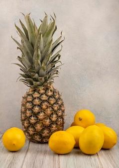 Vista laterale di frutta fresca come ananas e limoni isolati su una superficie grigia
