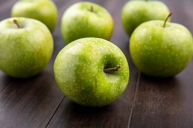 Vista laterale delle mele fresche e verdi isolate su una superficie di legno