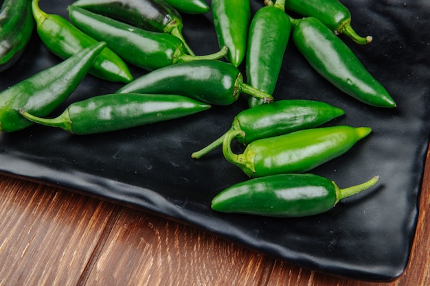 Side view of fresh green chili peppers on a black tray on wooden rustic surface