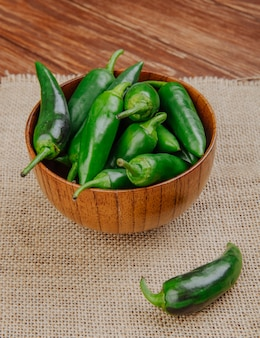 Side view of fresh green chili peppers in a wooden bowl on sackcloth on rustic surface