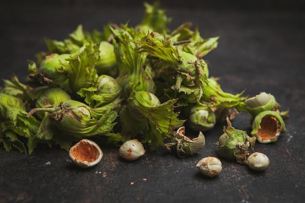 Nocciole verdi fresche di vista laterale su marrone scuro.
