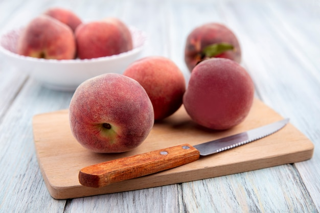Side view of fresh and juicy peaches isolated on a wooden kitchen board with peaches on a white bowl on grey wooden surface