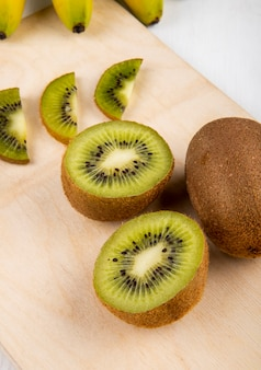 Side view of fresh kiwi fruit and slices of kiwi on a wood cutting board on white