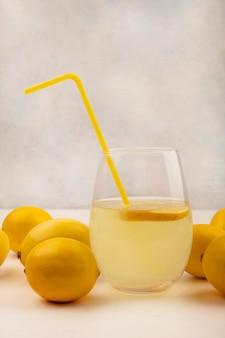 Vista laterale del succo di limone fresco in un bicchiere con limoni isolato su una superficie bianca