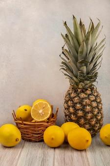 Vista laterale di limoni freschi su un secchio con limoni e ananas isolato su un grigio tavolo in legno su una superficie bianca