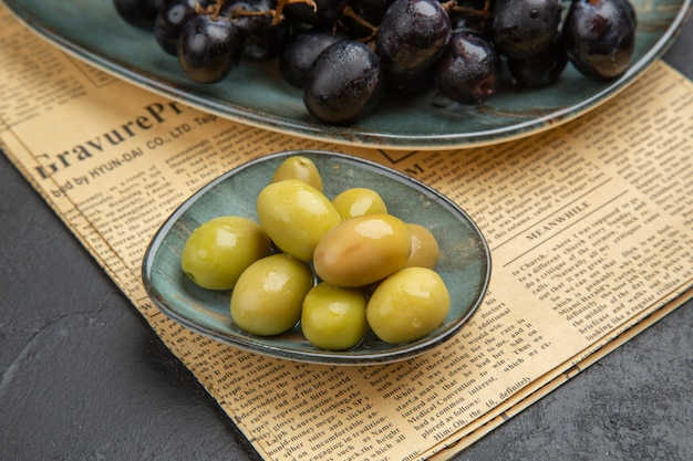 Side view of fresh organic green olives and bundles of black grape on an old newspaper on a dark background