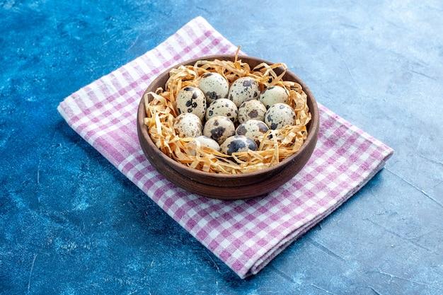 Vista laterale delle uova di allevamento di pollame fresco in un cesto di tessuto in una ciotola marrone su asciugamano spogliato viola piegato su sfondo blu