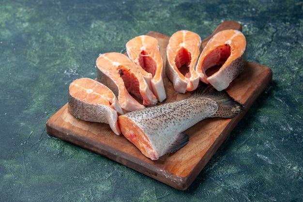 Vista laterale di pesce crudo fresco sul tagliere di legno marrone sulla tabella dei colori della miscela scura con spazio libero